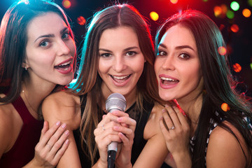 Girls having fun singing at a party