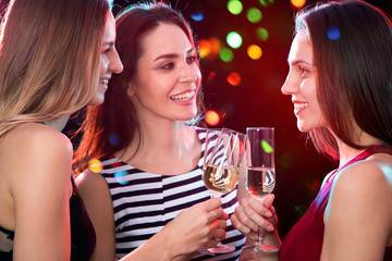 Beautifully dressed girls with glasses of wine at a Christmas party