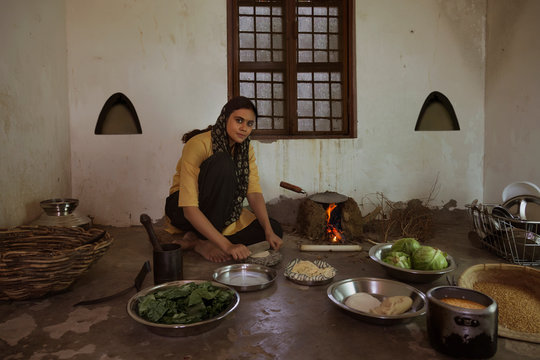 Rural woman cooking food on firewood in kitchen with utensils and vegetables on the floor.