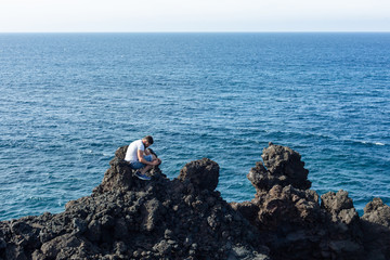 A tourist takes a photo squatting on a stone against the background of the sea.