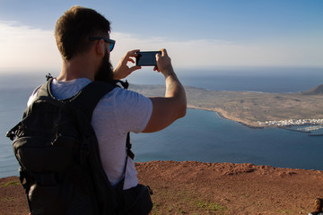 The man photographs an island in the ocean, standing on the edge of a cliff.