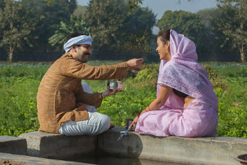 Happy farmer couple sitting near water tank having food in their agriculture field.
