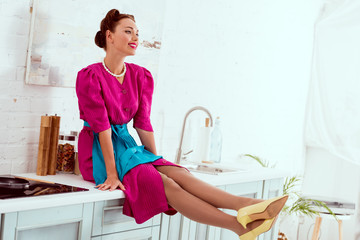 Smiling pin up girl sitting on kitchen table with stretched legs