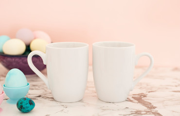 Two White Mugs Mockup - Easter theme. Easter eggs. Colorful eggs in matte colors. Light marble background