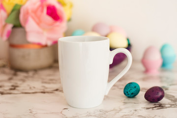 White Mug Mockup - Easter theme. Easter eggs. Colorful eggs in matte colors. Light marble background