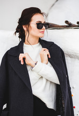 Fashion pretty woman model wearing a dark coat and white sweater, in sunglasses, posing over white background.