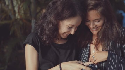 Wall Mural - two women laughingly examine pictures taken on camera