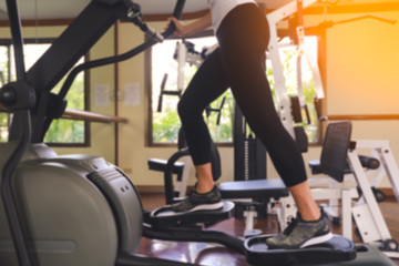 Blurred of young fit woman using an elliptic trainer in fitness centre,  Close up of legs of fitness girl in gym