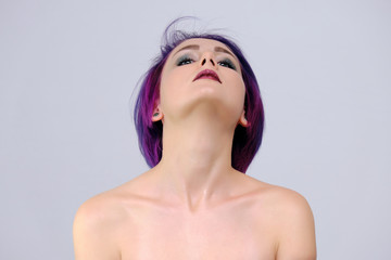 A beautiful, sexy girl with purple hair and a short haircut sits in the middle of the photo with a white background