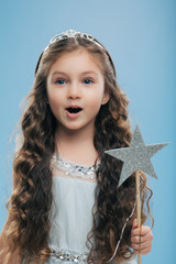 Small little child female princess wears crown and dress, holds magic wand, has long dark curly hair poses over blue background. Beautiful kid preapres for carnival or festive event. Childhood concept
