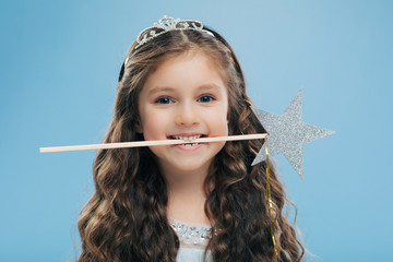 Horizontal shot of attractive smiling small kid holds magic wand in mouth, has brown curly hair, poses over blue background, looks directly at camera, wears crown. Children and magic concept