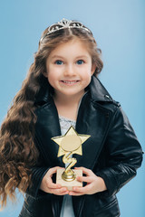 Positive smiling European child with blue eyes, long crisp hair, holds reward in form of star, wears black leather jacket, isolated over blue background. Image of happy girl poses indoor has good mood