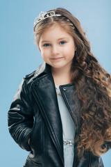 Isolated shot of beautiful Caucasian small child has blue eyes, long dark hair, keeps hands in pockets of leather jacket, isolated over blue background. Children, style, childhood, fashion concept