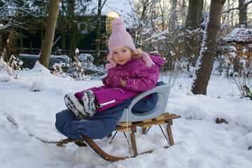 Kleines blondes Mädchen mit Mütze und Schneeanzug sitzt auf einem Schlitten im Schnee