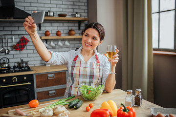 Attractive cheerful woman sit at table in kitchen. She takes selfie and pose on phone camera. Woman hold glass of white wine. Colorful vegetables on table.