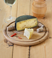 Kachotta cheese on a wooden board on a wooden background with wine in a glass and honey