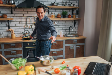 Cheerful man stand at stove and cook food in kitchen. He look at table and reach hand to it. Guy smile.