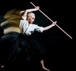 one caucasian bodoka fighters woman practicing Bo-Jutsu studio shot isolated on black background