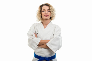 Portrait of female wearing martial arts uniform standing with arms crossed