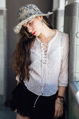 Beautiful ethnic hippie female looking down while standing inside apartment building after party