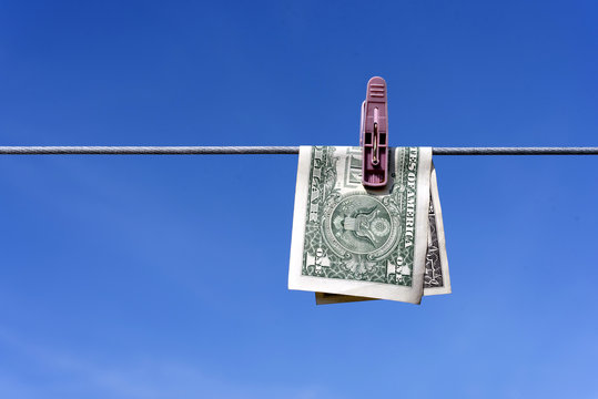 Money laundering of a one US Dollar bill note from the USA on a washing line with blue sky for AML Anti laundering finance business crime ideas