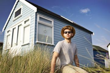 Young boy wearing sunglasses sitting near beach hut