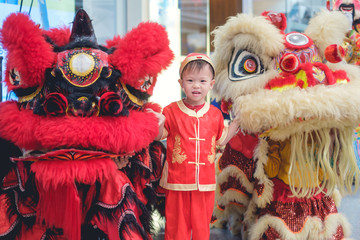 Cute smiling little 2 - 3 years old Asian toddler baby boy child in traditional red Chinese costume celebrating Chinese New Year with Chinese lion dance in Bangkok, Lunar New Year celebration concept Fototapete