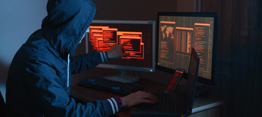 Hacker in the hood is pointing his finger at the display indicating the location of the cyberattack
