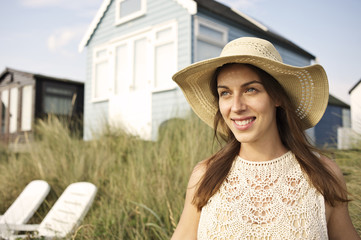 Smiling young woman wearing hat standing on beach