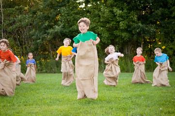 Happy Kids Having Potato Sack Race Outside