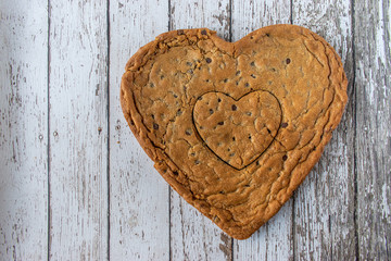 Huge Heart-shaped chocolate chip cookie on rustic wood table with copy space
