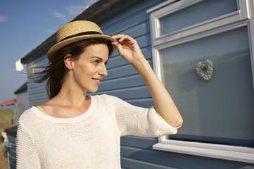 Smiling young woman wearing hat standing near beach hut