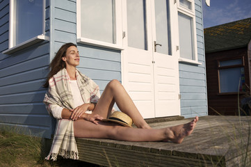 Young woman with eyes closed relaxing near beach hut