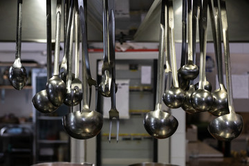 Silver spoons and steel tools in industrial kitchen. Gourmet restaurant before service, preparation and food processing concept. Master chef scene.