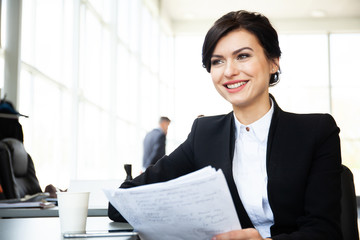 Business woman working in office with documents.