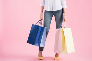 cropped view of girl holding shopping bags, isolated on pink