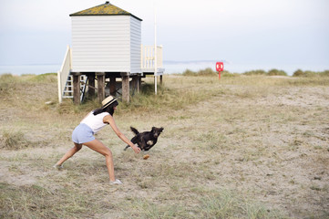 Young woman playing fetch with a dog at the beach