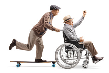 Elderly man on a longboard pushing a man with raised hand in a wheelchair
