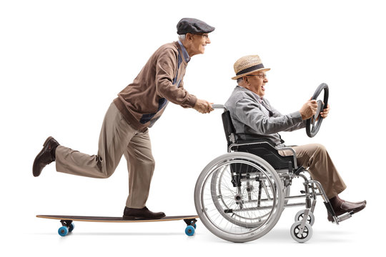 Elderly man riding a longboard and pushing a man holding a steering wheel and sitting in a wheelchair