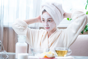 Beautiful happy woman with natural cosmetic mask on her face. Skin care and Spa treatments