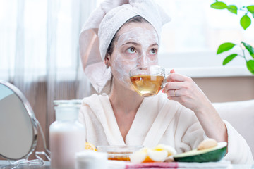 Beautiful happy young woman with natural cosmetic mask on her face. Concept skin care and Spa treatments