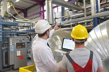 Arbeiter und Ingenieur in einer Industrieanlage // Mechanics repair a machine in a modern industrial plant - profession and teamwork