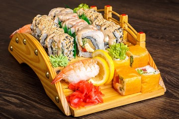 Red sushi sashimi set on a wooden bridge on a brown wooden table. With tune, prawn, shrimp, ginger, lemon