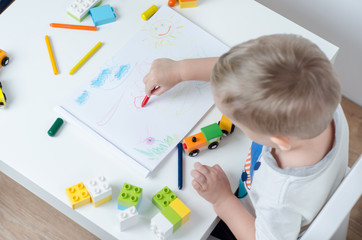 Little child draws in his album on a white table. Pencils, train, colorful plastic block in the children's room.