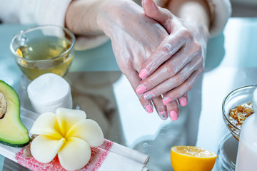 Woman applying the cream on her hands moisturizing them with natural cosmetics. Hygiene and care for the skin