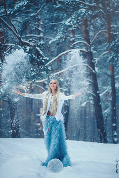 Winter Beauty Woman. Beautiful fashion model girl with snow hairstyle and makeup in the winter forest. Festive makeup and manicure. Winter Queen with snow and ice hairstyle