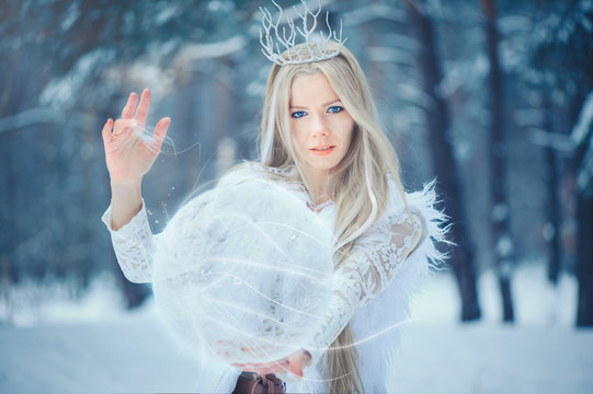 Winter Beauty Woman. Beautiful fashion model girl with snow hairstyle and makeup in the winter forest. Festive makeup and manicure. Winter Queen with snow and ice hairstyle. magic with snow