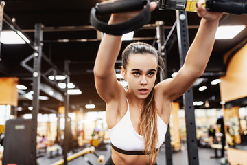 Bottom view - focused and strong-willed young female fitness model pumping her muscles through the pain in the gym. The concept of hard way to achieve its goal