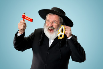 Portrait of a senior orthodox Hasdim Jewish man with wooden Grager Ratchet at Jewish festival of Purim at studio. The purim, jewish, festival, holiday, celebration, judaism, pastry, tradition, cookie