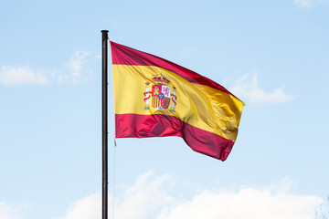 Spanish flag waving in the wind on blue sky